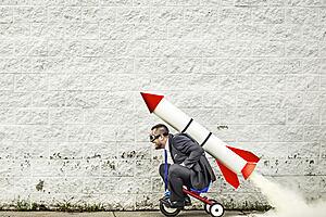 man riding toy rocket