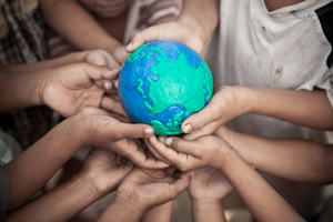 Children's hands holding a globe made of plasticine.