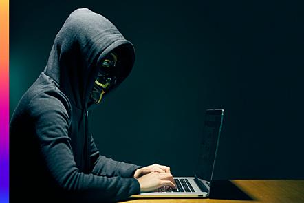 Figure in dark hood wearing a mask working on a laptop