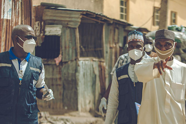Three men in Nigeria with protective masks on