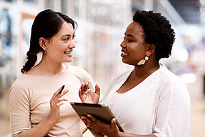 Two women talking and smiling, one is holding a tablet.