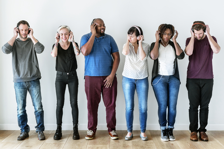 Six people of different genders and race are standing against a white wall wearing headphones and smiling