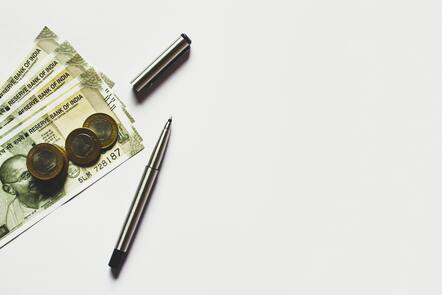 bills and coins on a white background and a pen next to them