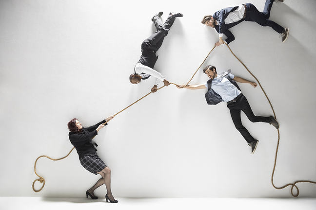Businesswoman pulling businessmen floating on rope against white background
