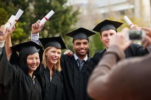 A small group of students celebrate graduating while a friend photographs their celebration