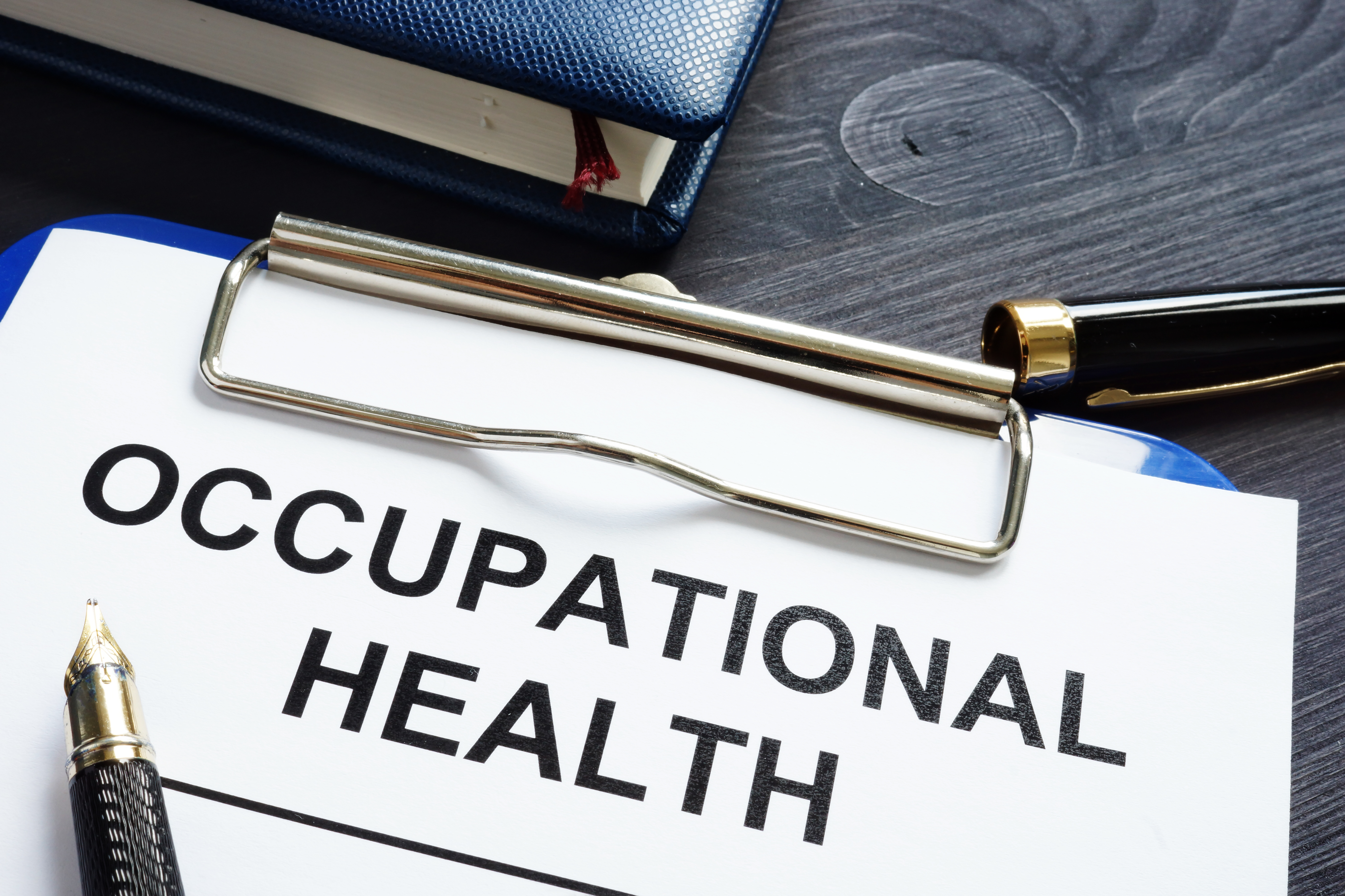 Illustration sheet with Occupaional Health written on it on a clip board and a pen lying next to it