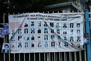 A banner affixed to a fence and displaying photographs of people missing and presumed dead as a result of the war in Kosovo 1998-99