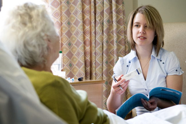 A carer going through some paperwork and medication with a resident at her bedside