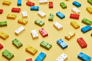 A selection of different LEGO Braille Bricks on a yellow table