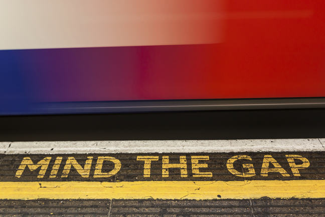 Photo of a train carriage next to Mind The Gap painted on the platform.