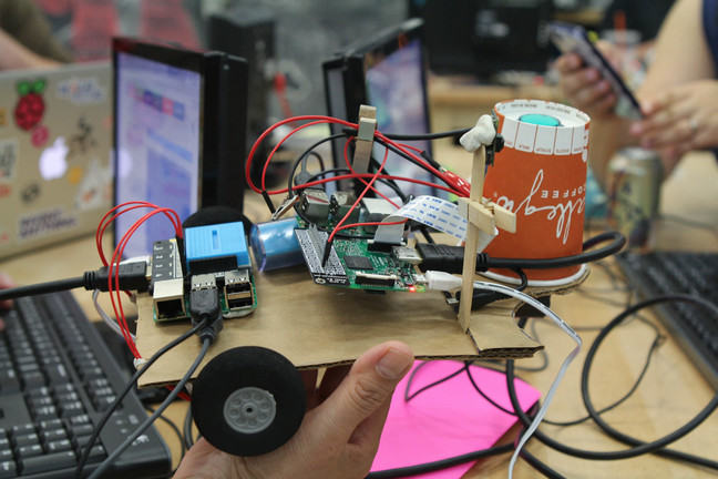 A prototyped robot buggy, being held by the team who created it