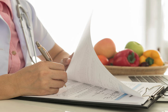 Health worker completing paperwork with basket of fruit and vegetables in the background.