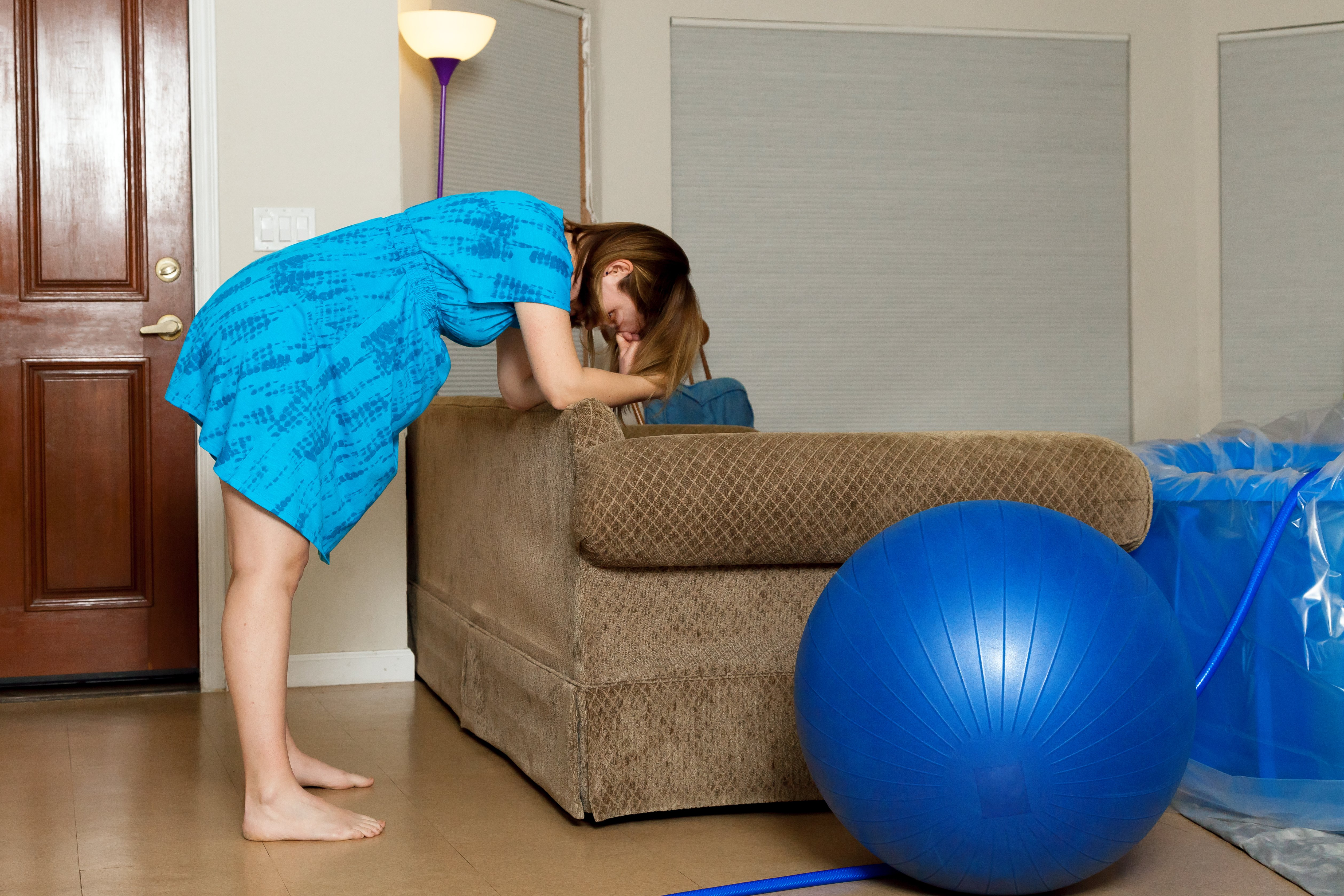 Pregnant woman leaning on couch