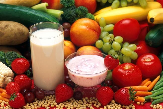 A platter of fruit and vegetables with a glass of milk and bowl of yogurt