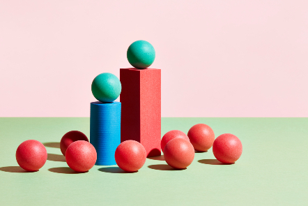Colourful balls on the ground, with two on plinths