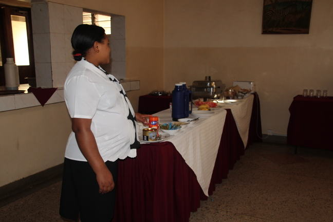 A pregnant woman working at a hotel, standing next to the breakfast buffet.
