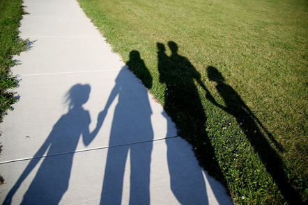 Shadow on grass of a family group, 2 adults and 3 children