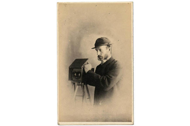 Man in a hat with a stereo camera with two lenses, on a tripod, his left hand resting on top of the camera.