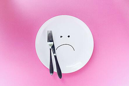Image of an empty plate with a sad face drawn on in marker pen.