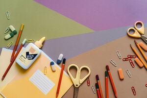 An arrangement of paper, scissors, pencils and clips