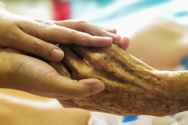 Older person's right hand in hands of a younger person