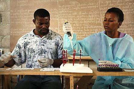 A Haitian man and woman sit next to each other at a table. Behind them is a blackboard covered in writing. Both people are wearing gloves as they are testing blood for malaria and LF. The woman who is wearing a blue gown pipettes blood into an RDT.