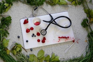 Chopping board with stethoscope and berries in a test tube.