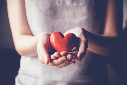 Two hands hold a wooden heart.