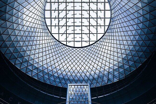 Looking up into a carefully constructed transparent dome made from a curved grid of simple elements