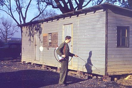 A man wearing khaki overalls operates an insecticide sprayer. The pack is carried on his back, and he is using the handheld nozzle to spray an insecticide on the outside walls of a small bungalow house made of brown wood.