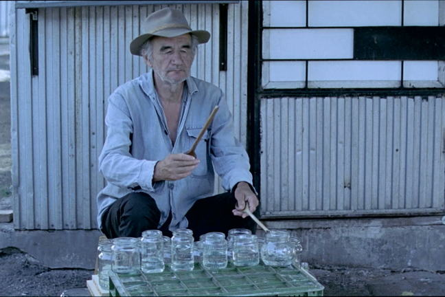 Old man character from the film *Szalontudo* playing the jam jars with drum sticks