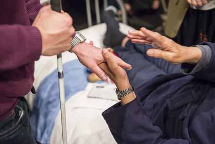 Image of elderly person's hand holding support cane