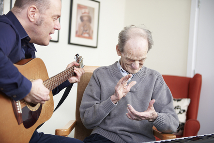 A male music therapist is singing and playing guitar while an elderly man is clapping