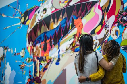 two women holding each other in front of a colourful wall
