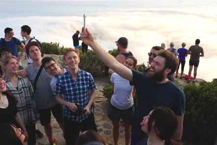 Decorative image, a group of people standing on a mountain, one person is holding a device up in the air for others to look at. Go Global 2016, Cape Town