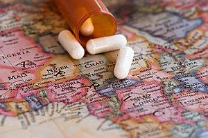 A map of Africa with a bottle of pills on top