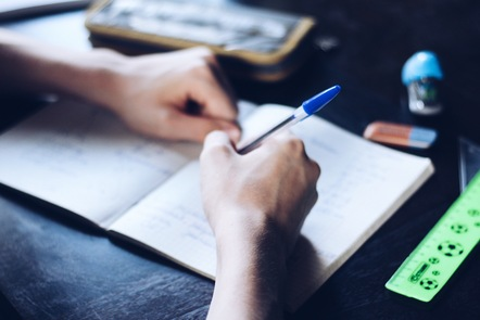 A person is writing in a notebook with a blue Biro pen