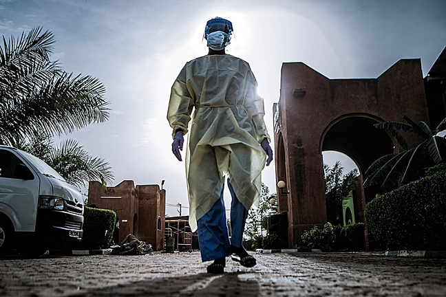 A nurse returning from her shift screening patients in Niger, dressed in personal protective equipment.