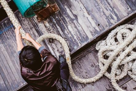 A person pulling a thick rope on a ship