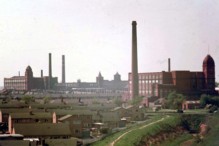 Taken from slightly raised land and looking across relatively new housing towards two of the giant mills which used to characterise Leigh