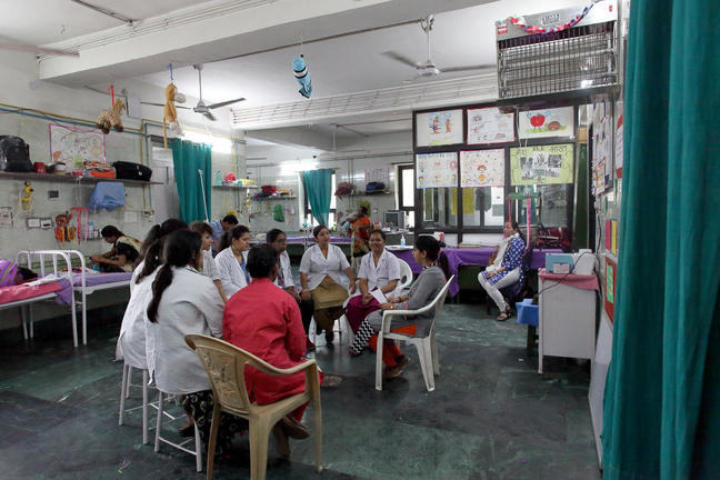Hospital staff sit in a circle in the middle of a ward in a hospital in India for a staff meeting