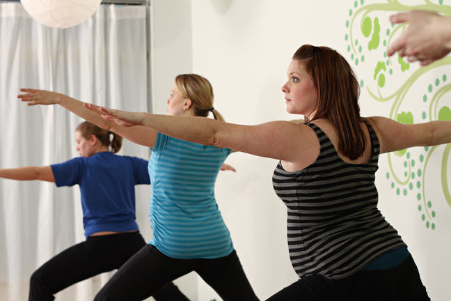 Three pregnant women perform yoga stretches