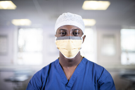 A medical student wearing scrubs and a face mask