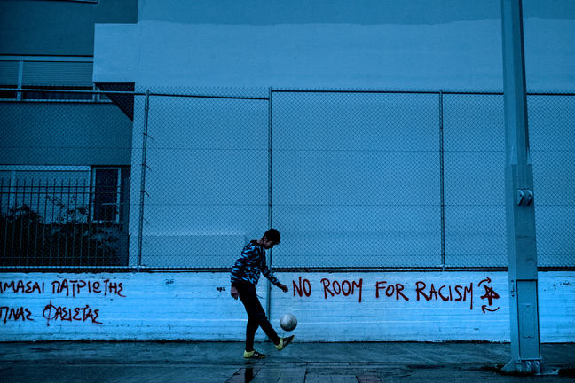A teenage boy in a sweatshirt, tracksuit and running shoes is kicking a football with his left foot. Behind him is a short wall with a wire fence on top with graffiti that says 'No Room for Racism'.