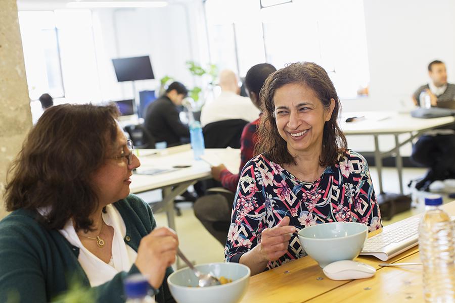 Happy businesswomen eating lunch in office