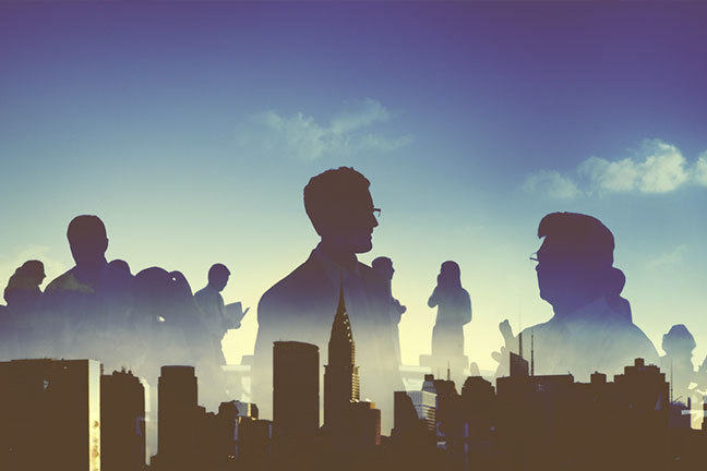 Silhouettes of people over urban setting