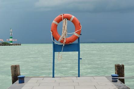 Orange life ring by sea.