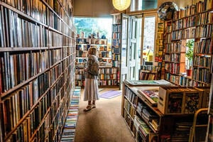 A woman in a bookshop in Edinburgh, staring at the shelves.