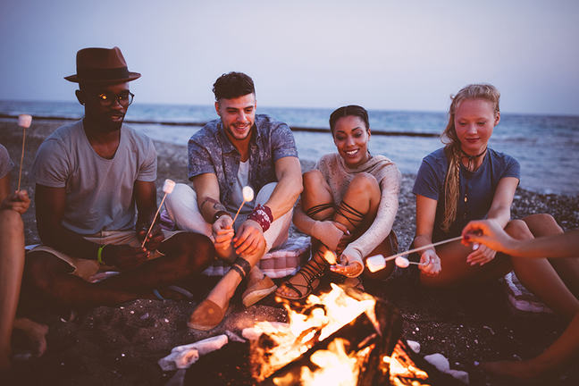 diverse group of six young adults roasting marshmellows over a campfire at the beach
