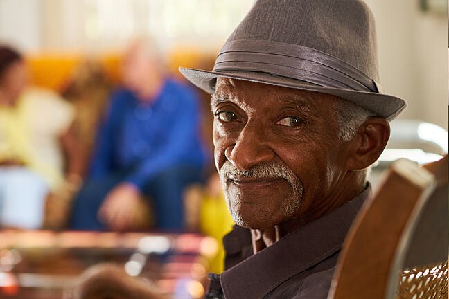 Elderly man wearing a hat looking into the camera